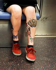 Ink on the Subway (Scott Yeckes) Tags: nyc newyork newyorkstory people qline tattoo angels aypclub legs manhattan onthesubway ribbons skullbutterflies streetphotography subway symmetery tattoos underground unique unusual voyer