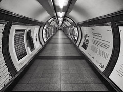 Inexorable (Douguerreotype) Tags: london monochrome tube uk symmetry blackandwhite underground urban british mono city tunnel britain subway metro bw gb england