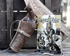 A Gun, And A Song (jah32) Tags: gun revolver holster leather colt45 peacemaker gunbelt innercowboy songsoftheplains cowboy cowboysongs songbook western desaturation antique