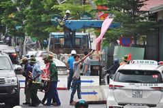 Coming through... (Roving I) Tags: flags warnings traffic workers workmen sunhats equipment gear generators street barriers danang vietnam