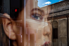 Mysterious look. Seen in Lugano, Switzerland. (Phototravelography) Tags: lugano switzerland shoppingwindow eyes blue sky reflection mystery woman lady church