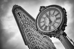 Fifth Avenue Building clock with the Flatiron Building in New York City, USA (Tim van Woensel) Tags: flatiron avenue building clock ny nyc new york big apple skyscraper usa us united states america fuller fifth manhattan national historic landmark bw black white cityscape north clouds