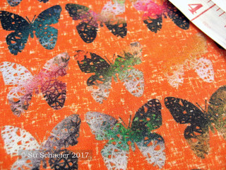 'Dark and stark butterflies on hot wind-whipped orange by Su_G' close up on basic cotton