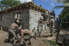 Sailors work with Kosraean workers to construct the Health Clinic in Micronesia.