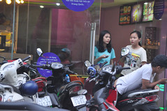 Where are all the customers? (Roving I) Tags: girls waiting doorways entrances shops stores fastfood dining motorcycles street cellphones danang vietnam