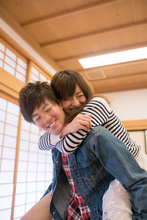 Young woman playing with her boyfriend in Japanese tatami room.