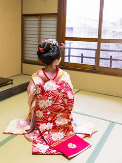 Maiko girl sitting on heels in Japanese tatami room