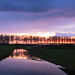 Dutch spring evening (M a u r i c e) Tags: sunlight sunset horizon polder pond water trees silhouettes reflections sky nature landscape fence longexposure