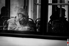 Man On Bus (BigRedTroll) Tags: absorbed architecture bw blackandwhite bus cap man monochrome people reflection structuralelement structure window canon g10