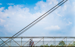 Simpler Days (Colour Version) (relishedmonkey) Tags: nikon d5300 colour 35mm 18g india kerala students kids two friends sky blue clouds bridge cycle wheels walking design architecture outdoor day sunny sun lines straight engineering people