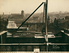 Tyne Bridge in the very early stages of construction (Tyne & Wear Archives & Museums) Tags: tynebridge tyneside northeastengland bridges newcastleupontyne gateshead stmaryschurchgateshead civilengineering blackandwhitephotograph industry industrialheritage archives buildingthetynebridge unitedkingdom bridge land city urban construction structure building 22march1927 landmark iconic jamesbaconsons march1927october1928 jamesgeddie chiefassistantengineer dormanlongcoltd middlesbrough impressive spectacular unusual interesting fascinating clock hand sky grain mark chimney roof wall bolt metal rail beam cog handle rope knot pin arc letter number label identification blur smoke daylight shadow civilization progress view glimpse crossing infrastructure design artanddesign abstract cylinder brick stone support platform