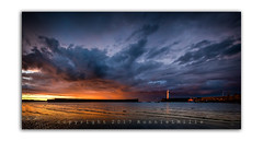 Fire in the Hole!! (RonnieLMills) Tags: donaghadee harbour lighthouse sunset underlit clouds fiery tones low tide water beach