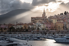 Menton - an unexpected spectacle (Rafael Zenon Wagner) Tags: nikon d810 70200mmf4 70mm frankreich france côte d'azur küste bucht hafen sonnenuntergang sonne strahlen gold licht palmen meer boot stadt bunt fassade gegenlicht spiegelung wolken gelb grün lila türkis coast bay harbor sunset sun rays light palm trees sea boat city colorful facade backlight reflection clouds yellow green purple turquoise