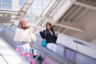 Young business women saying hello eatch other on escalator