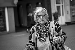 It Blows (Leanne Boulton) Tags: urban street candid portrait portraiture closeup streetphotography candidstreetphotography streetportrait candidportrait eyecontact candideyecontact streetlife action motion movement timing elderly old woman female face facial expression look emotion feeling mood atmosphere eyes wind weather windy gust hair tone texture detail depthoffield bokeh naturallight outdoor light shade shadow city town scene human life living humanity society culture canon 5d canon5d 5dmarkiii 70mm character ef2470mmf28liiusm black white blackwhite bw mono blackandwhite nuneaton warwickshire england uk dutchangle
