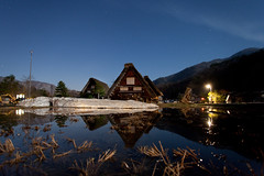 Ogi-machi village at night (Mikey Down Under) Tags: japan ogimachi shirakawago japanese village historic world heritage site night photography moonlit moonlight evening water reflection rice field stalks snow gessho style home house thatch roof timber stars