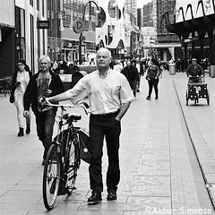 Walking the bicycle (Akbar Simonse) Tags: holland netherlands nederland denhaag thehague lahaye sgravenhage streetphotography streetshot straatfotografie straatfoto man fiets bicycle tricycle bakfiets people candid zwartwit bw blancoynegro bn monochrome vierkant square squareformat akbarsimonse