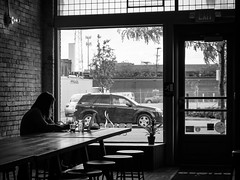 Table for One (tim.perdue) Tags: table for one single alone solitary girl woman person figure street candid brioso coffee shop columbus ohio window door brick wall light shadow silhouette stool glass laptop macbook coffeehouse black white bw monochrome discovery district downtown urban city long st explore interesting popular interestingness explored panasonic lumix gx85 35100mm cafe