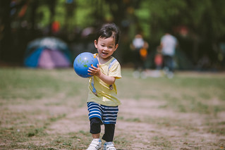 Small boy playing ball with on meadow in the park