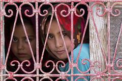 Behind the window (RubénRamosBlanco) Tags: humanos humans niñas girls hermanas sisters guapas beautiful cute smile sonrisa curiosidad curiosity ventana window retrato portrait color viajar travel amazigh tribus tribes valledelziz zizvalley marruecos morocco