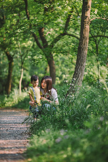 Front view of mother and her son crouching on footpath in forest