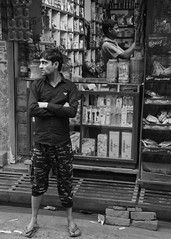 indian man standing in front of shopkeeper (VineetJT) Tags: india street shopkeeper shop men grandmother candid nikon d7100 afs dx 1685mm f3556 nikkor varanasi black white digital banares