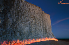 The Cliff is on Fire (Gavmonster) Tags: nikon nikond7000 d7000 gswphotography landscape sky land sussex uk unitedkingdom lighttrails lightpainting pixelstick longexposure 30seconds night evening flames cliff sevensisters eastsussex beach pebbles chalk rocks sea orange blue fire englishchannel southdowns