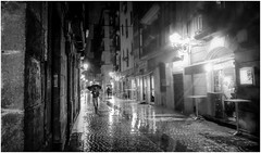 Looking for distraction (VandenBerge Photography (On/off ....but mostly off) Tags: umbrella streetscene street bilbao thebasquecountry blackandwhite mono people rain weather wet bars spain europe atmosphere night