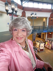 What Does A Girl Do When It's Chilly, Blustery, Rainy Outside? (Laurette Victoria) Tags: gray raincoat pink mall milwaukee bayshoremall woman laurette