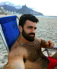 1315 (rrttrrtt555) Tags: hair hairy chest muscles beard necklace chain chair lounge beach water ocean attitude arms armpit speedo swimwear sand selfie masculine stare drawstring eyes legs outdoors rocks clouds shoulders shorts waves play