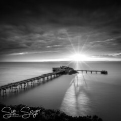 Casting a Shadow. (Explored 27.04.2017) (Sue Sayer) Tags: pier old birnbeck weston somerset sunburst mono monochrome uk outside contrast sunlight clouds sunset coast