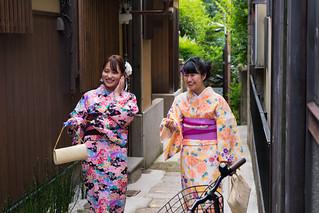 Happy women in kimono walking on narrow path in Kyoto