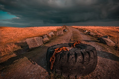 Left behind (MooziX) Tags: tyre old chain rusty field stones rocks space cloudy clouds grey sunset shadows landscape wide angle road path travel explore wanderlust orange black blue abandoned scenics no people cornwall uk