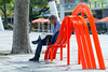Stranger on a chair (bhoyracer1) Tags: canon ef100mm thinking ponder thought concentration newspaper london orange art wobbly seating resting southbank street metro