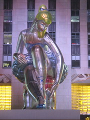 Seated Ballerina Mylar Balloon at Night 6223 (Brechtbug) Tags: seated ballerina mylar balloon night art sculpture by jeff koons 2017 rockefeller center nyc 30 rock new york city standing up above ice rink gold prometheus statue giant decoration ornaments 05202017 nights nite nites lights lites light oversize load ornament summer spring kids toy kitsch 60s toys sculptures statues pretty evening lobby plaza plant plants plastic artist
