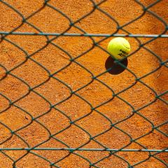 forgotten (Rosmarie Voegtli) Tags: tennis ball fence grid square dornach orange yellow play sport shadow