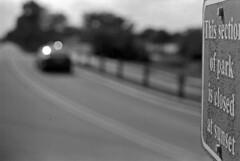 Weathered Sign (PositiveAboutNegatives) Tags: leica leitz leicaflexsl vintagecamera slr 60mm leicar sign signage park film analog grain bokeh efke bw blackandwhite coolscan nikon9000scanner 60mmelmarit weathered old