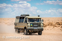A desert vehicle makes it was through the Namib desert in Namibia, Africa. (Remsberg Photos) Tags: africa namibia namib desert vehicle driving inmotion auto passengers dust trail sand landscape clouds empty solitaire nam