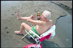 (Beaches Brew) (Robbie McIntosh) Tags: leicamp leica mp rangefinder streetphotography 35mm film pellicola analog analogue negative leicam elmarit analogico leicaelmarit28mmf28iii elmarit28mmf28iii dyi selfdeveloped filmisnotdead autaut candid bellinifotoc41 kodakportra160 kodakportra portra kodak beach tan seaside bathers strangers swimsuit lidomappatella mappatellabeach singer man radio beer peroni tanninglotion