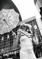 R0029176 (G. L. Brown) Tags: bridgestonearena facepaint parasol stilts woman nashville nashvillestreetphotography tennessee america streetphotography blackandwhite bw