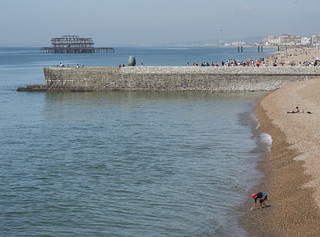 Brighton Seafront With Woman In Foreground Collecting Water In A Bottle