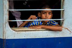 Indian boy leans out train of train window (Photos-by-Jamie) Tags: boy train trainwindow scars india railway child darkeyes framed portrait hardlife soulful