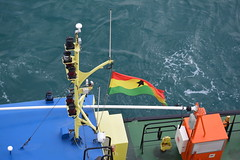 OUR PILOT,  LOME.  AND THE FLAG OF TOGO, AFRICA. (vermillion$baby) Tags: africa blue boat color done flickr green lome orange people red togo tug yellow ocean sea westafrica togosea port atlantic atlanticocean ship workboats bow water travel world international boatthings boatstuff things boatthingsf colora