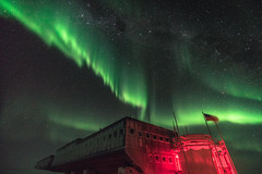 South Pole Station, Aurora, and the Milky Way (redfurwolf) Tags: southpole southpolestation auroraaustralis aurora milkyway night stars nightsky sky antarctica antarctic flag building out nat nightphotography redfurwolf sonyalpha a99ii sony sal1635f28za