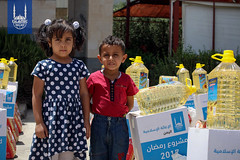 Two children next to their Ramadan food parcel in Yemen.