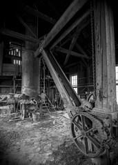 At the Foundry (trainmann1) Tags: nikon d90 amateur handheld summer june 2017 eastbroadtop eastbroadtoprailroad ebt rail railroad heritage historic antique relic abandoned neglected rusty crusty rust crust dirty orbisonia pa pennsylvania rockhill rockhillfurnace train trains bw blackwhite blackandwhite desaturated buildings interior inside foundry crane gears beams metal steel hardwork labor melting smelting melt form create vignette tokina 1116mm