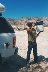 Desert gas station (dataichi) Tags: gas station oil tank filling bucket cowboy rancher ranchero people hat car desert ranch heat baja california sur mexico travel tourism
