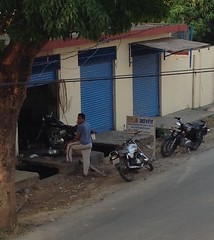 image (Veee Man) Tags: appleipad una himachalpradesh india bharat street road building automechanic garage person man customer candid stand three 3 motorcycle blue trees plants sign