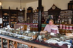 The Apothecary (Mister Oy) Tags: blsitshill ironbridge davegreen oyphotos ©oyphotos victorian apothecary shop store vintage heritage lady female shopkeeper chemist old fujixpro2 fuji1024mm produce goods forsale clock counter
