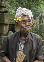 The temple attendant (tmeallen) Tags: elderlyman temple attendant buddhism flowersoverear wetricegrains forehead whiteheadcovering whitebeard glasses lightrain goagajahtemple ubud bali indonesia elephantcave